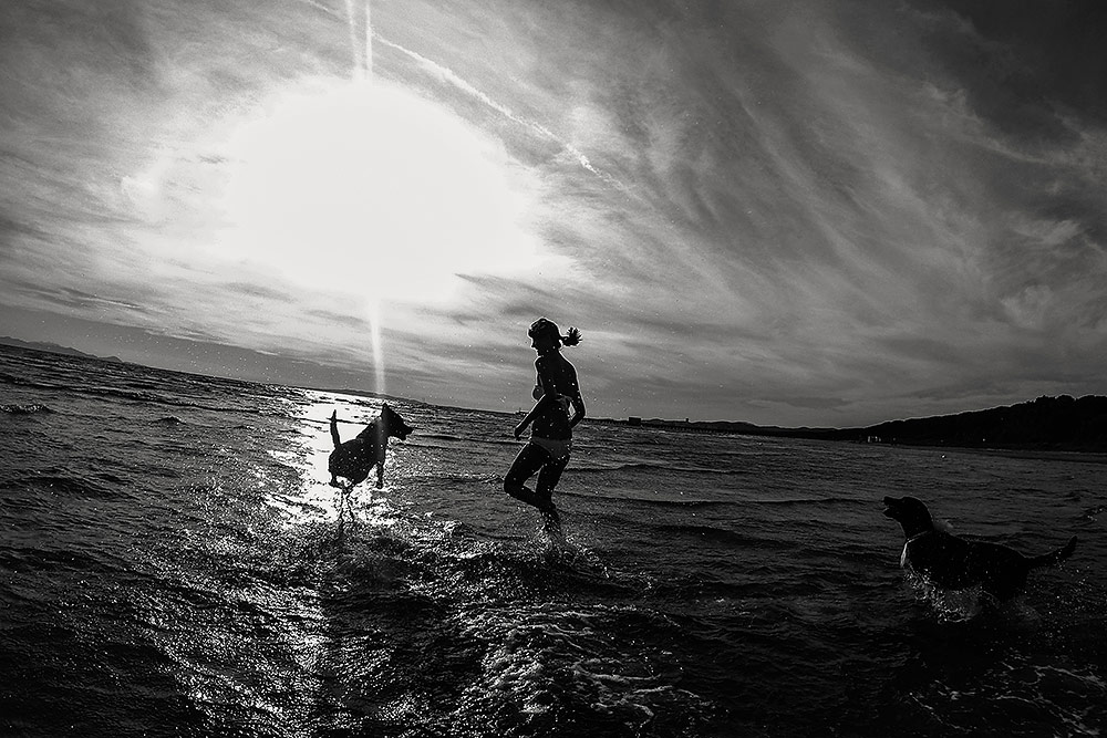 beach wedding in tuscany, bride playing in water with their dogs