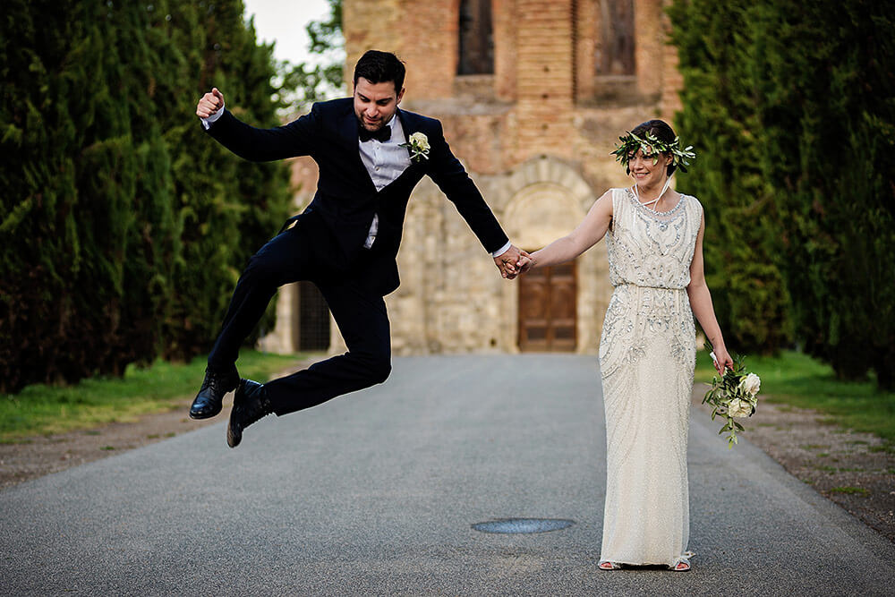 groom jumping with bride in front of san galgano
