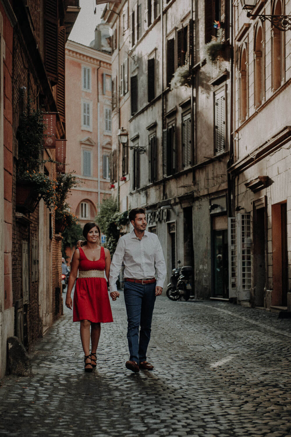 engaged couple walking in historic center of rome, engagement photographer in rome
