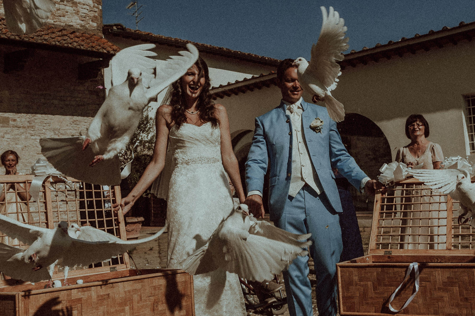happy tuscany wedding couple with doves