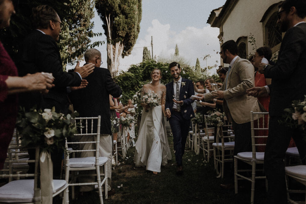 newlyweds walking in the aisle with launch of confetti, florence wedding