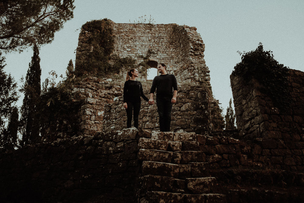 Engaged couple portrait in ancient castle, in Val d'Orcia Tuscany