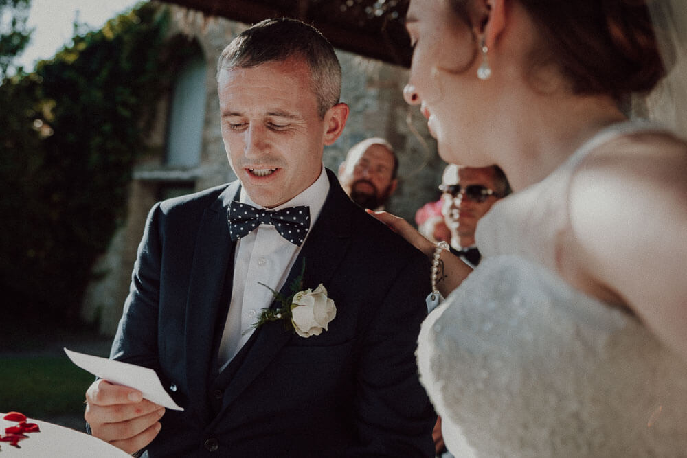 destination wedding in tuscany: groom read the wedding vows