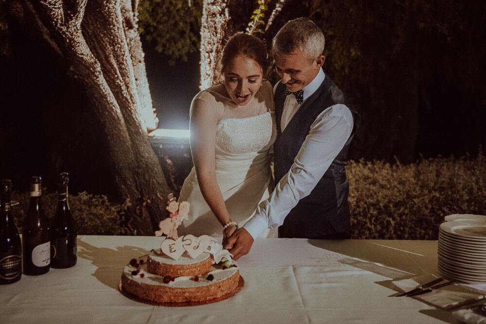wedding in monteriggioni, tuscany: bride and groom cutting the cake