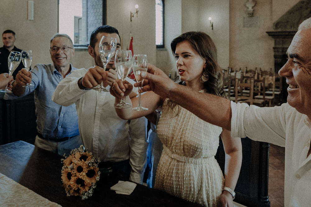 married couple in the town hall of cortona are having a toast